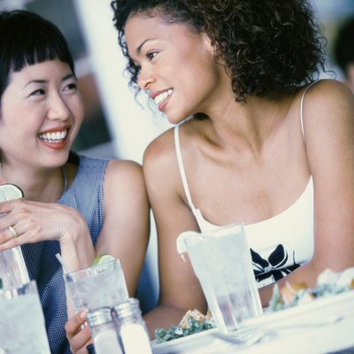 Two young women seated at a table smiling