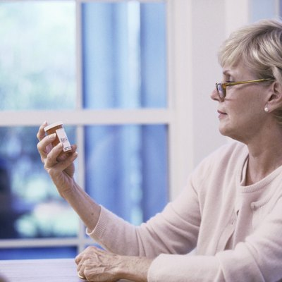Senior woman reading the label on a pill bottle
