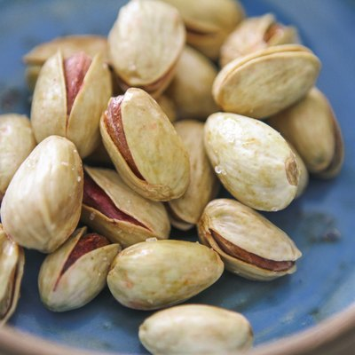 Lemon and safran roasted salted pistachios in a blue bowl