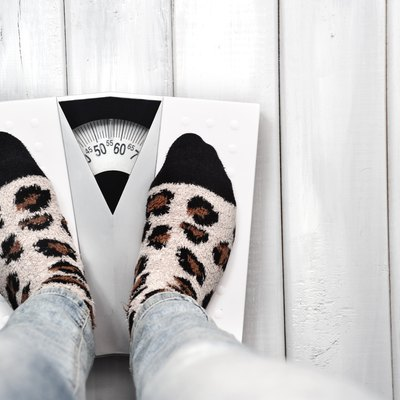 Woman on weight scale in casual clothes