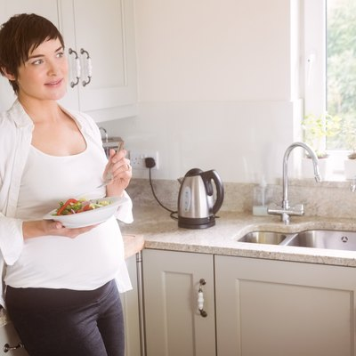 Pregnant woman having bowl of salad