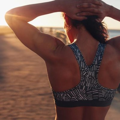Rear view shot of muscular woman in sports bra standing outdoors with her hands on her head at sunset.