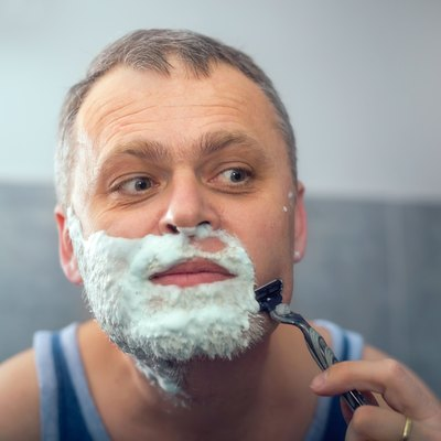 Middle aged man shaving in bathroom
