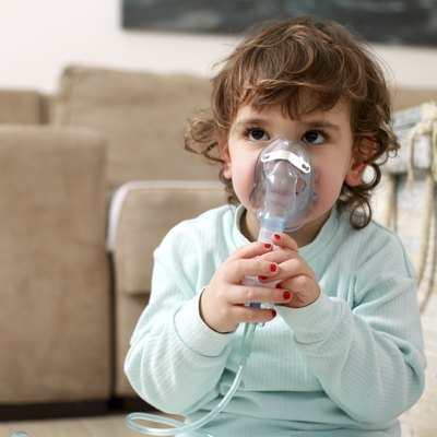 Portrait of a little girl with inhaling mask