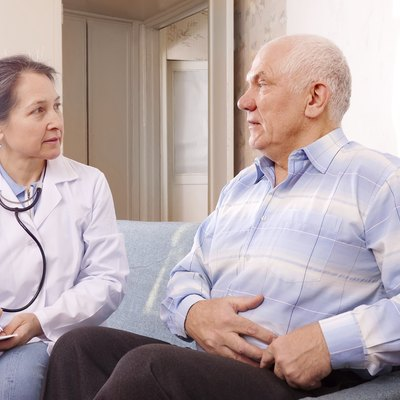 man complaining  to doctor about stomachache