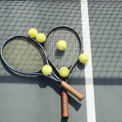 Tennis racquets and balls lying on court
