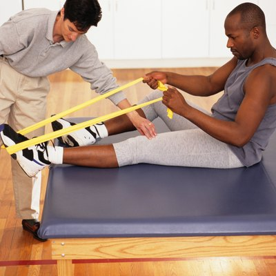 Man bending forward in physical therapy centre, woman supervising, elevated view