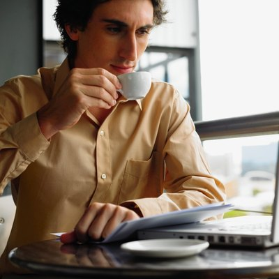 Young businessman using laptop sitting at table drinking coffee