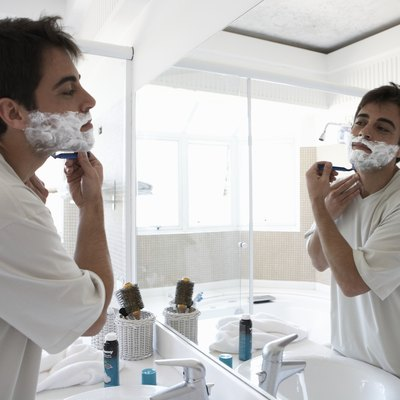 Man shaving face in bathroom mirror, side view