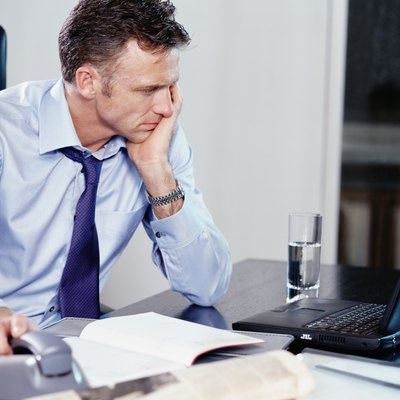 Businessman using laptop at desk, resting hand on phone