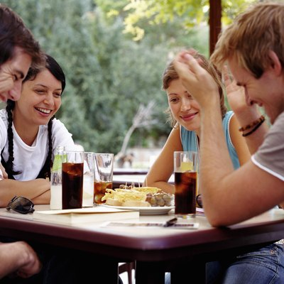 Two couples relaxing at outdoor cafe, smiling