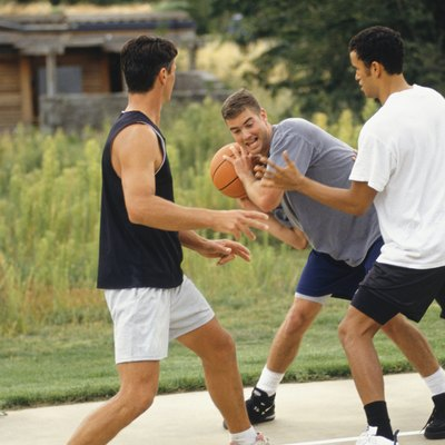 Three teenage boys (16-17) playing basketball on outdoor court