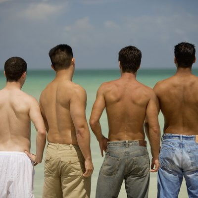 Rear view of four men standing on the beach