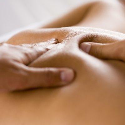 Hands massaging back of a woman