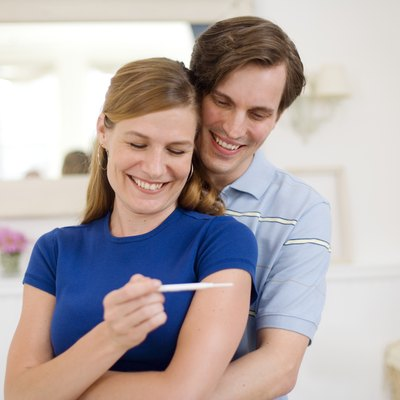 Happy man and woman with pregnancy test