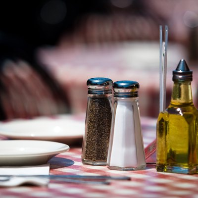 Salt and pepper shakers and olive oil on restaurant table