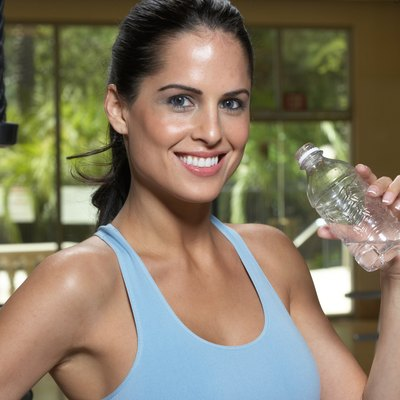 Woman drinking water from bottle in gym, smiling, close-up, portrait