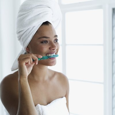 Young woman with a towel around her head brushing her teeth