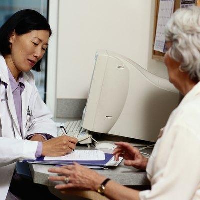 Doctor writing prescription for mature female patient