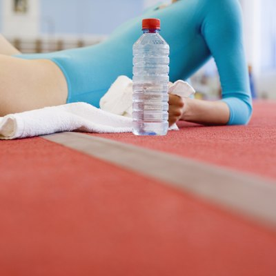 Young gymnast resting with bottled water