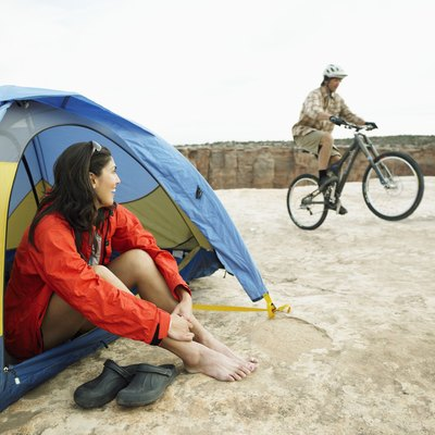 Woman sitting in tent, man riding mountain bike in background