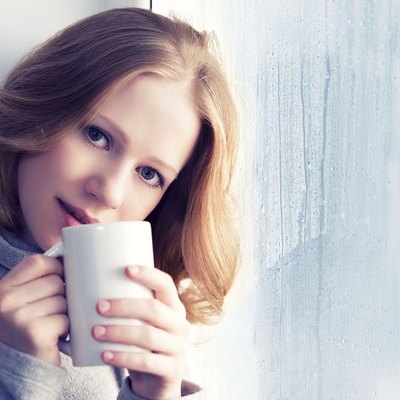 beautiful dreamy young woman with a cup of hot coffee