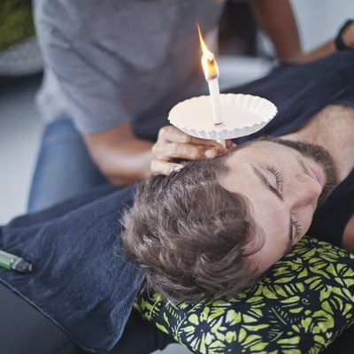man having an ear candle therapy