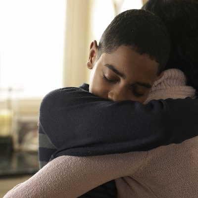 Boy (12-13) hugging mother at home