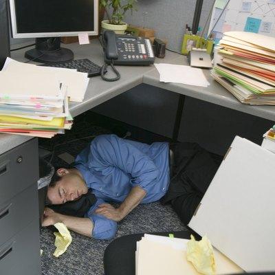 Businessman sleeping in cubicle