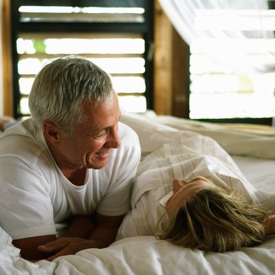 Senior couple smiling at each other in bed, close-up