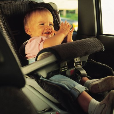 Baby sitting in a car seat and clapping hands