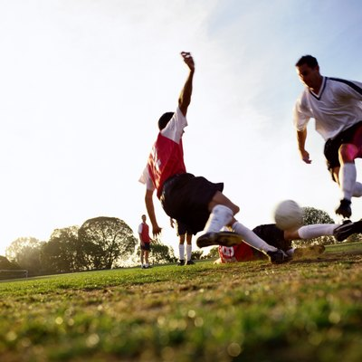 Soccer players tackling for ball, ground view