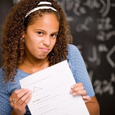 Disappointed teenage girl student holding test