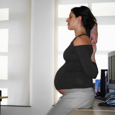 Pregnant young woman stretching by desk, profile