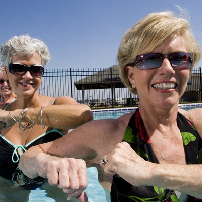 Cheerful senior women exercising in swimming pool