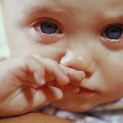 Close-up of a baby boy crying and rubbing his nose