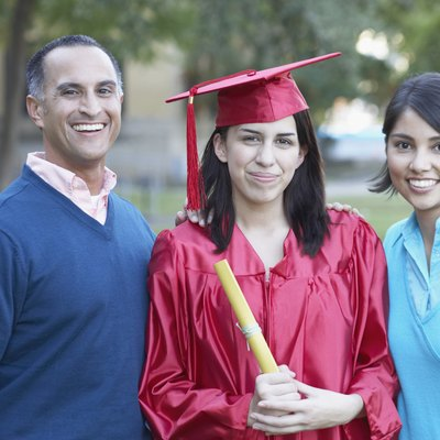 Portrait of a female graduate standing with a mid adult man and a young woman
