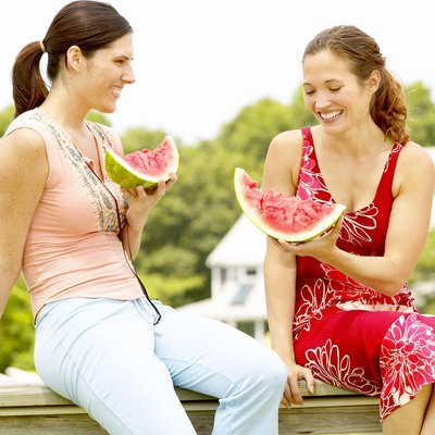 Women eating watermelon outdoors