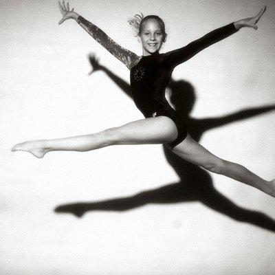 Portrait of a female teenage gymnast jumping