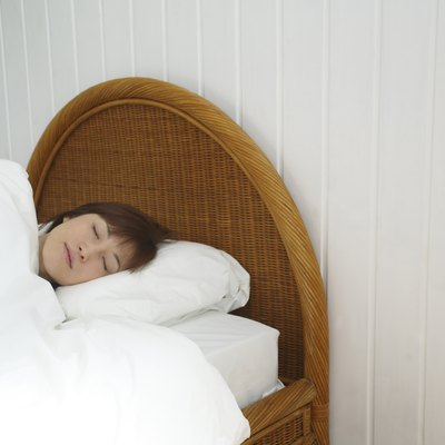 Young Woman Sleeping in Bed, Front View
