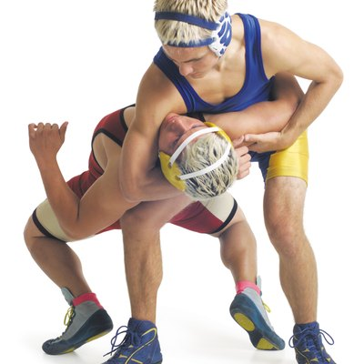 two teenage caucasian male wrestlers from opposite teams fight as the one in blue puts a choke hold on the one in red