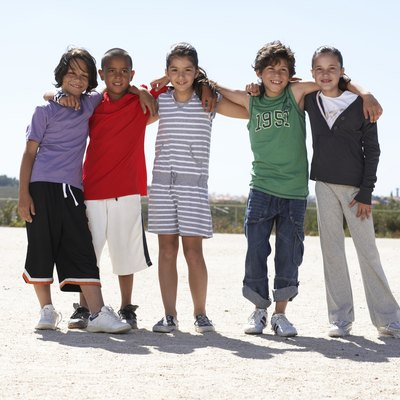 Group portrait of children (9-12) embracing outdoors