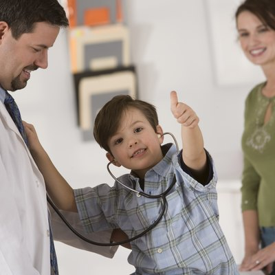 Boy giving thumbs-up while using stethoscope on doctor