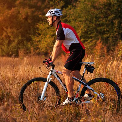 cyclist man cycling on a rural road during sunset