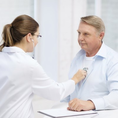 female doctor with old man listening to heart beat