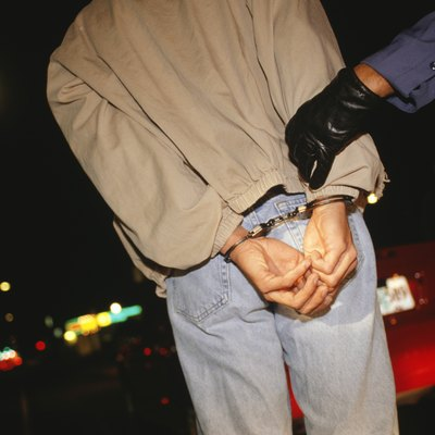 Teenage boy (16-17) getting handcuffed, rear view, mid section