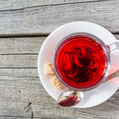 Hibiscus tea in glass cup, rustic wood background