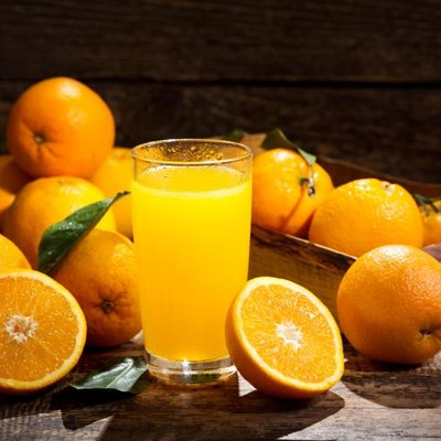 glass of orange juice with fresh fruits on wooden background
