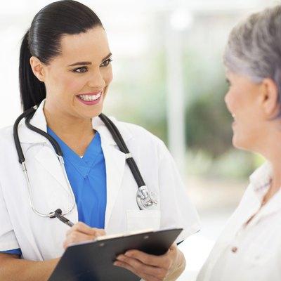 pretty young nurse talking to senior patient