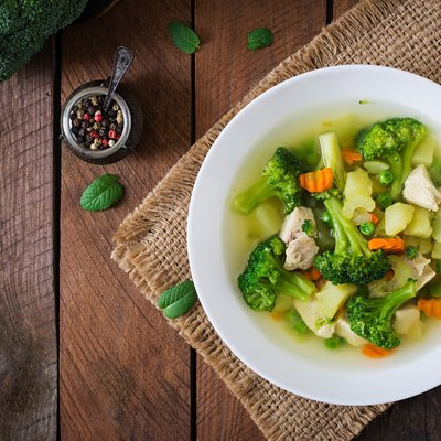 Chicken soup with broccoli, green peas, carrots and celery